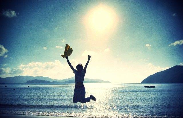晴れた日の海でジャンプする写真